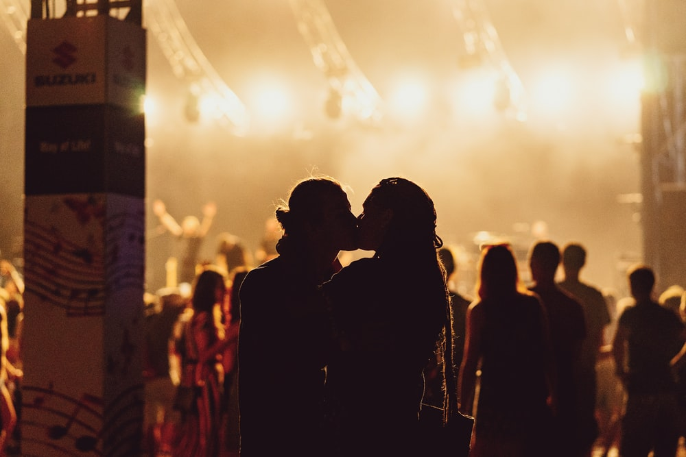 man and woman kissing in the middle of concert