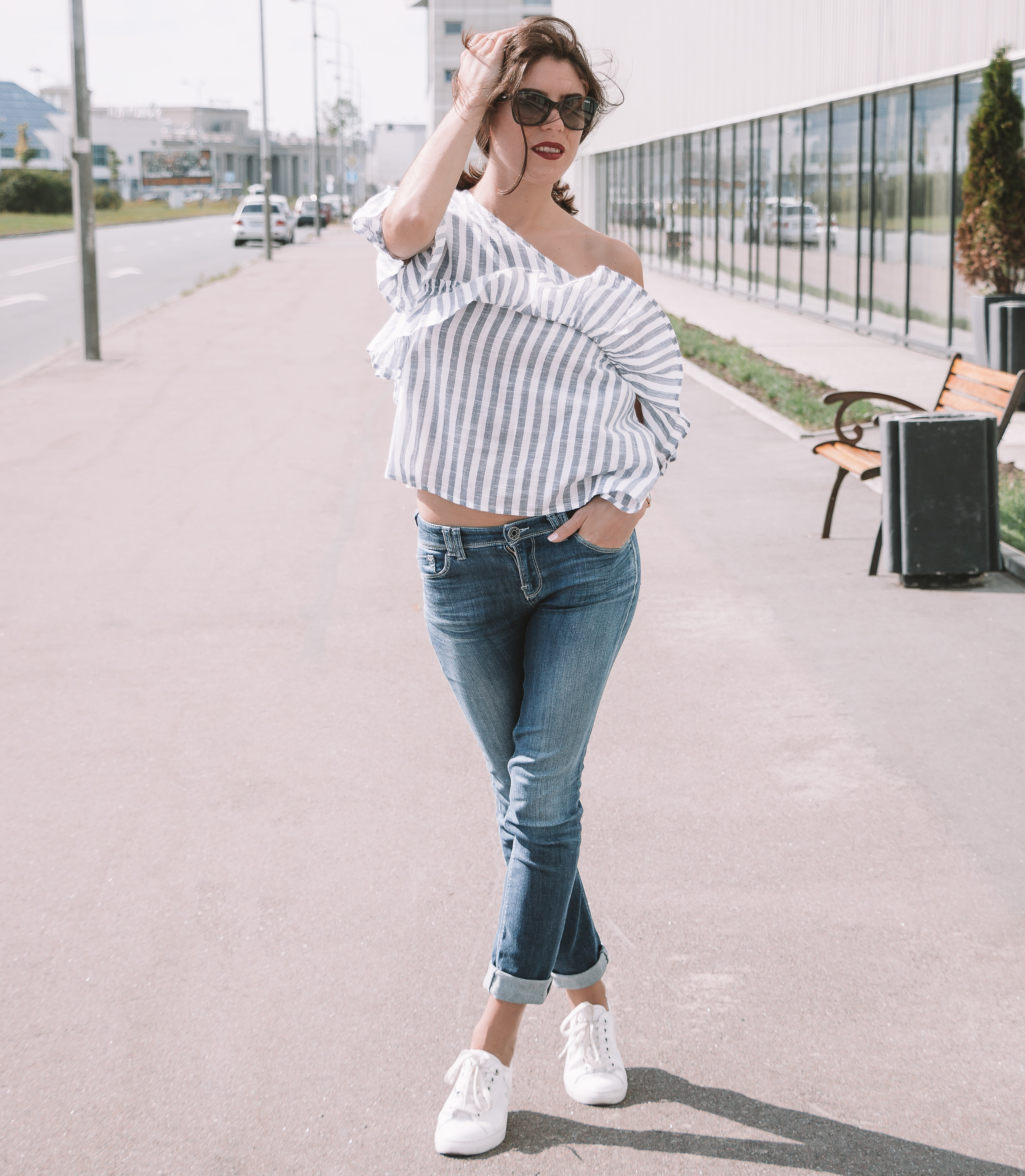 woman in white and gray vertical striped blouse and blue denim jeans wearing sunglasses standing beside road during daytime