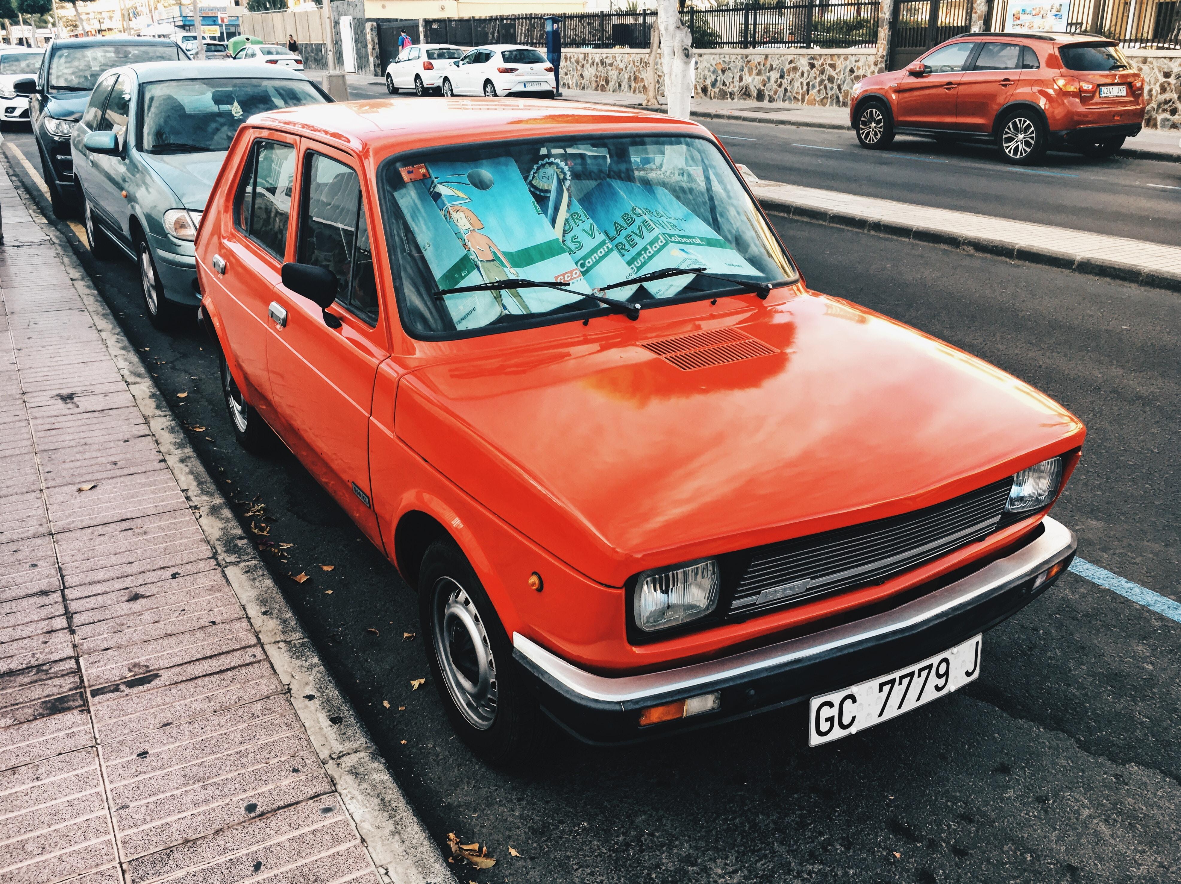 red 5-door hatchback parked near concrete curb