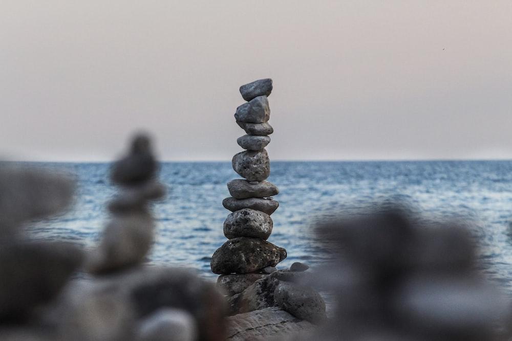 rock balancing near body of water