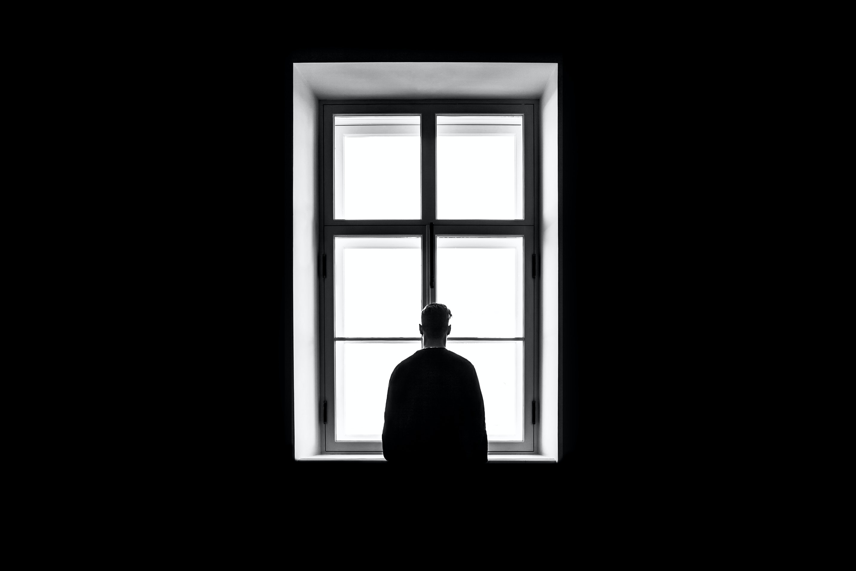 man standing in front of the window dreaming of a better life