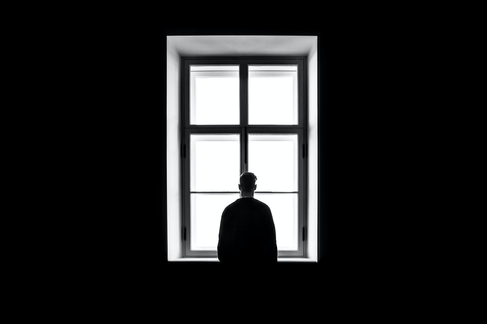 man standing in front of the window