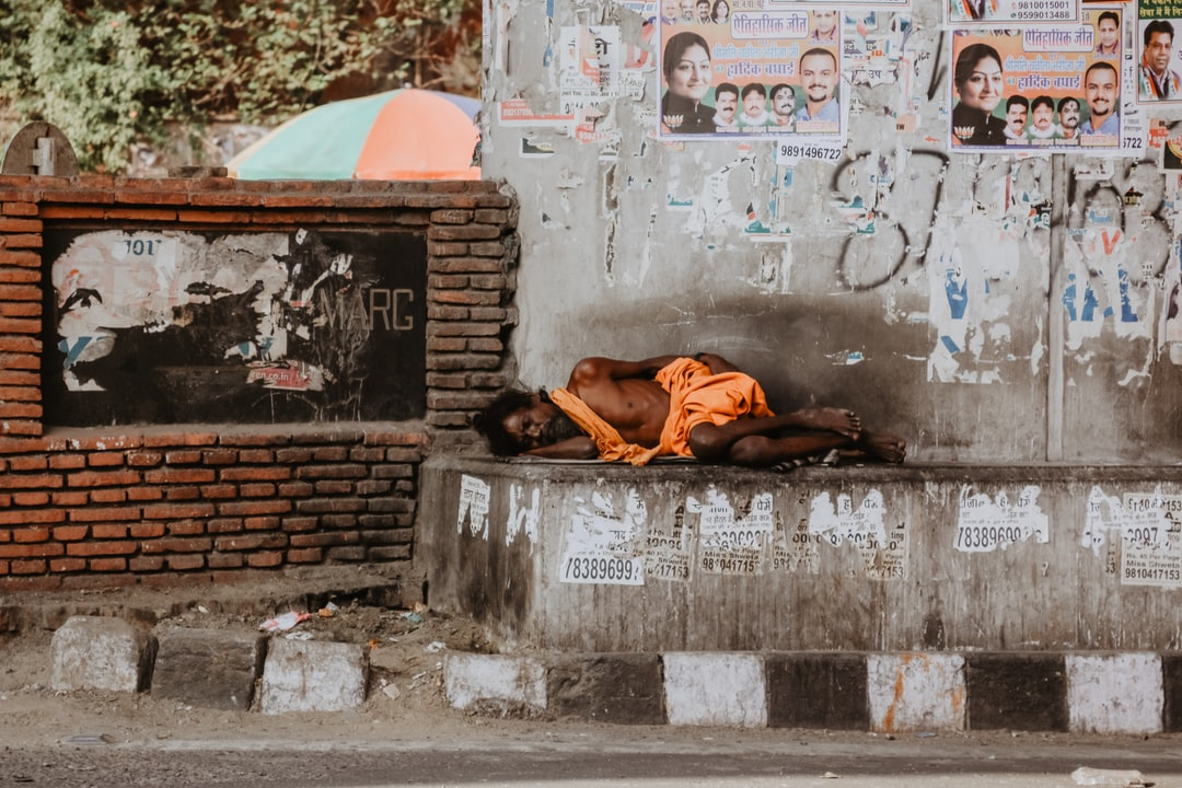 A poor homeless man sleeps by a temple