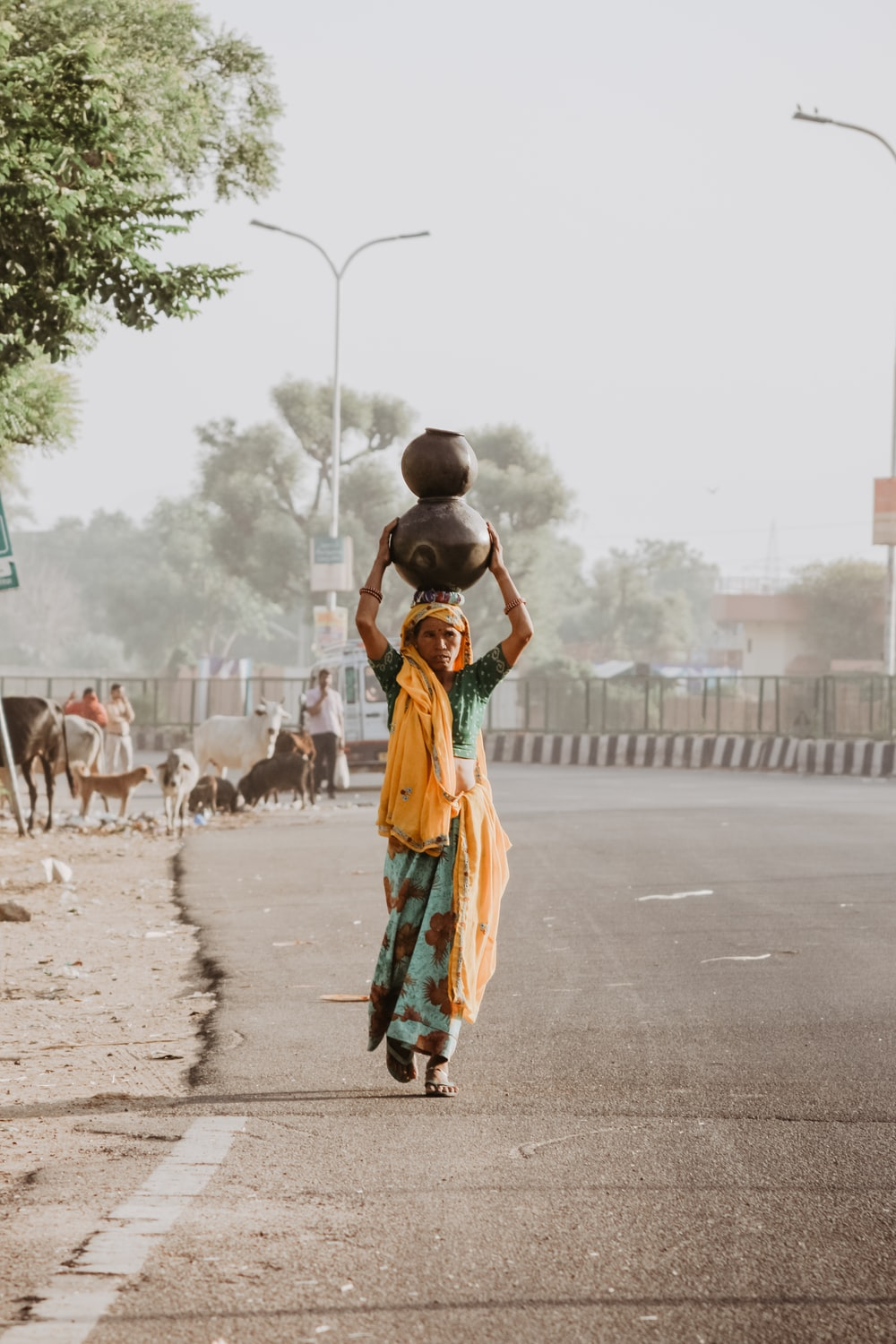 woman walking on road carrying two jars on head