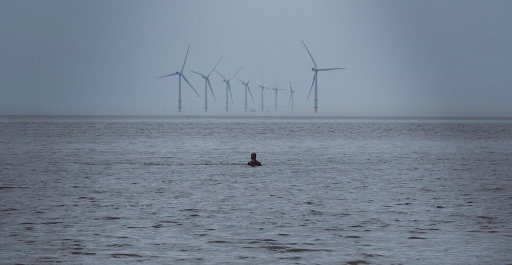 person swimming on water near windmills