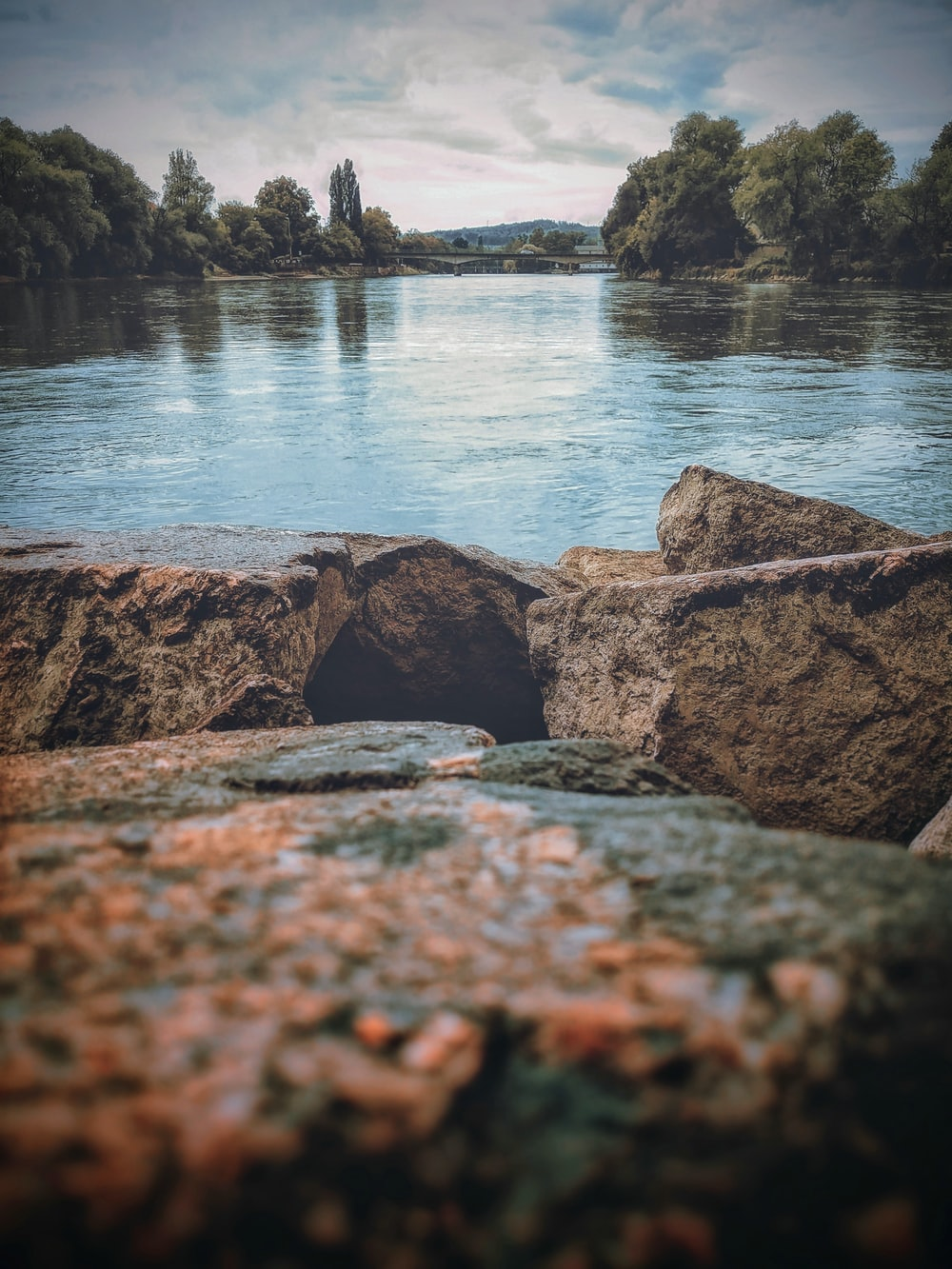 low-angle photography of stones near body of water at daytime