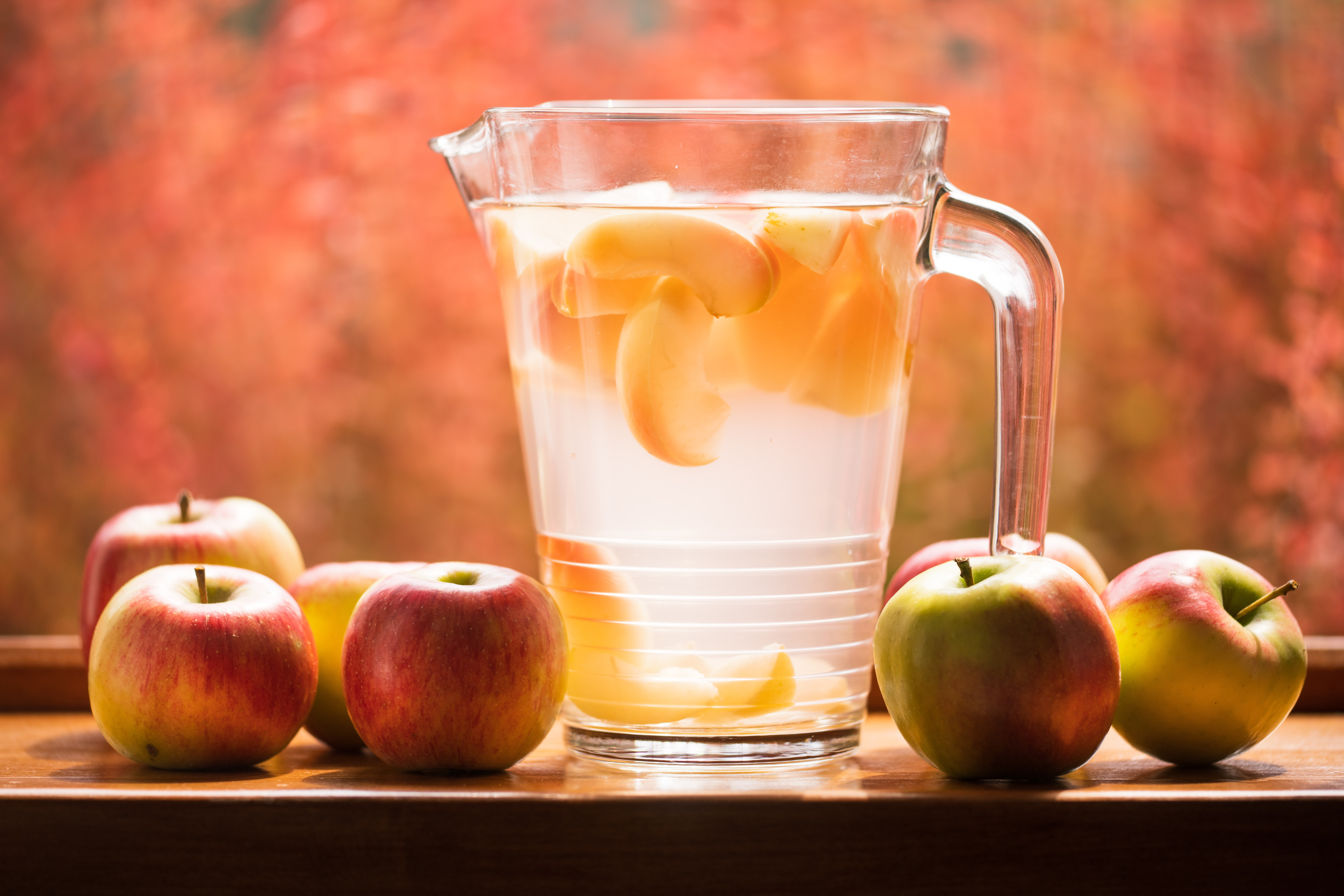 glass pitcher and apples on table