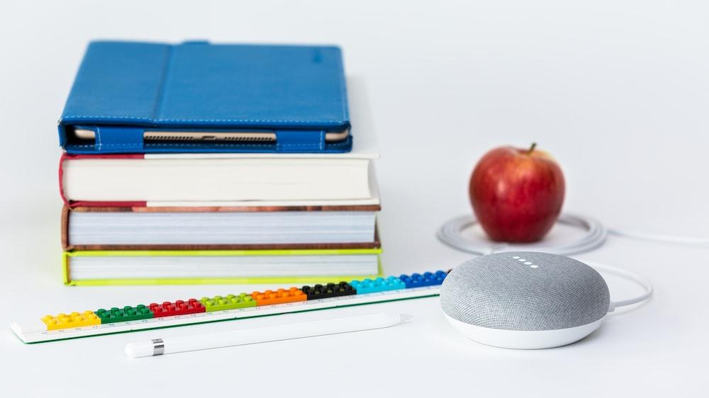 honeycrisp apple fruit near books and chalk Google Home Mini smart speaker