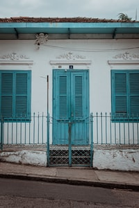 white and teal concrete house at daytime
