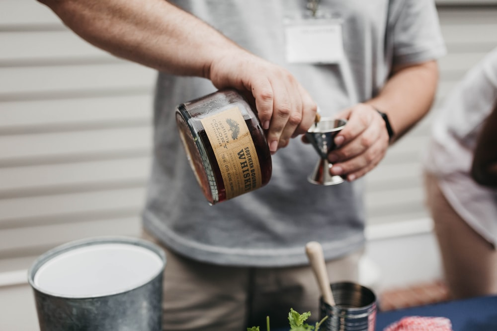 person pouring whiskey on goblet