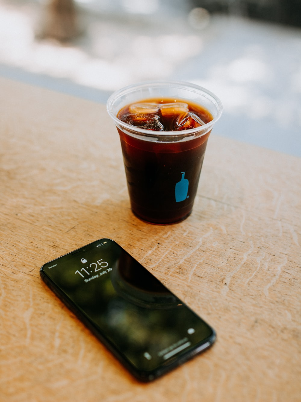 black iPhone 7 beside clear disposable cup filled with beverage with ice cubes
