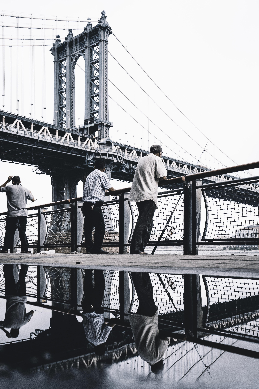 three men standing near bridge