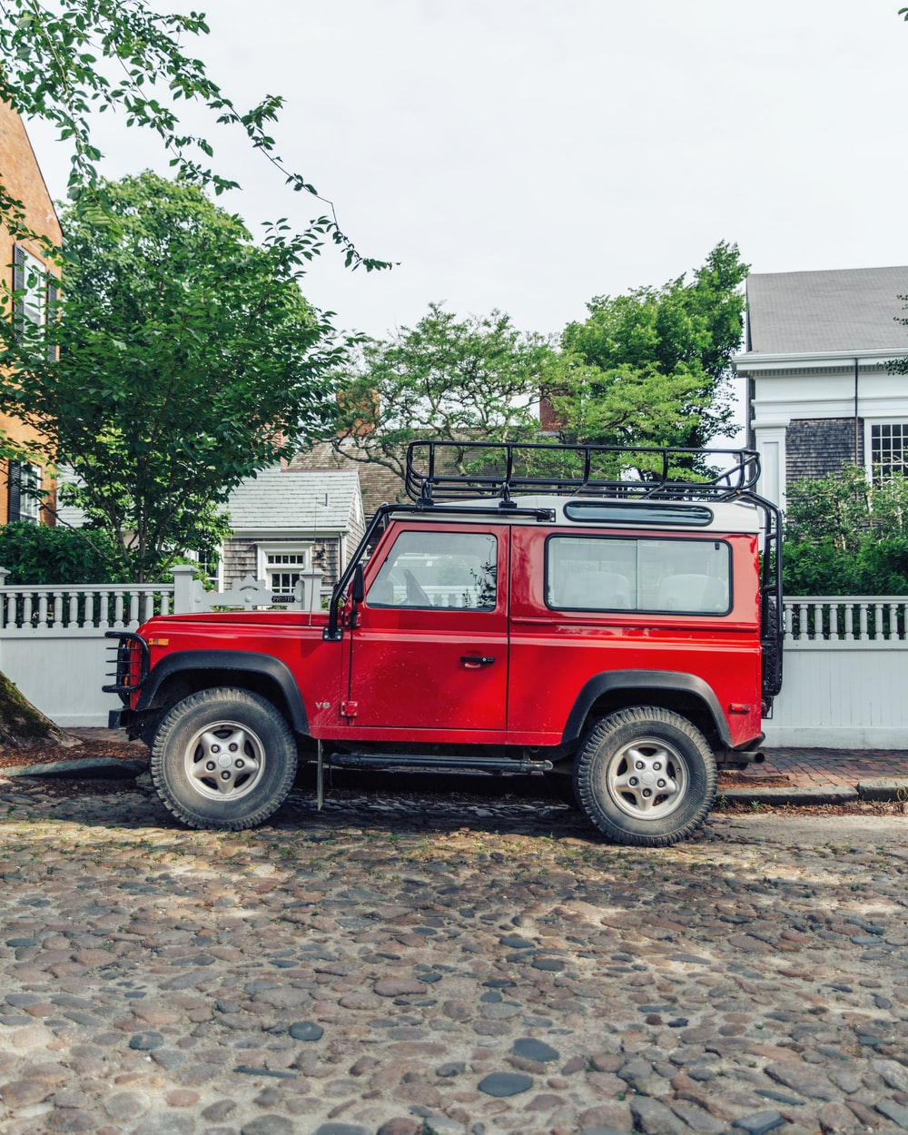 red off-road car parked at sidewalk