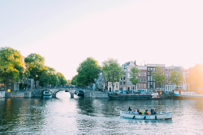 people riding canoe beside concrete bridge at daytime