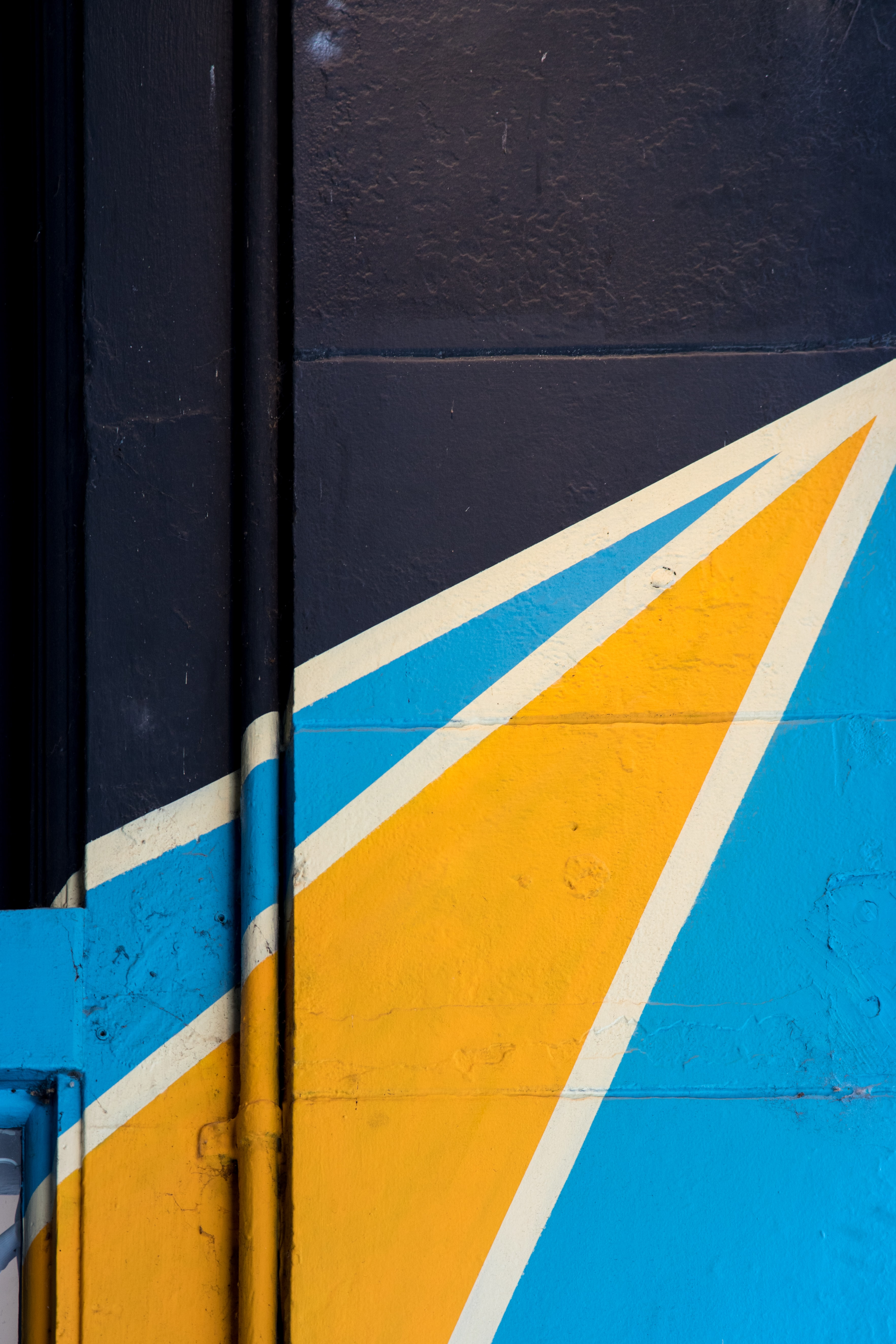white, blue, and yellow mural painted on building wall
