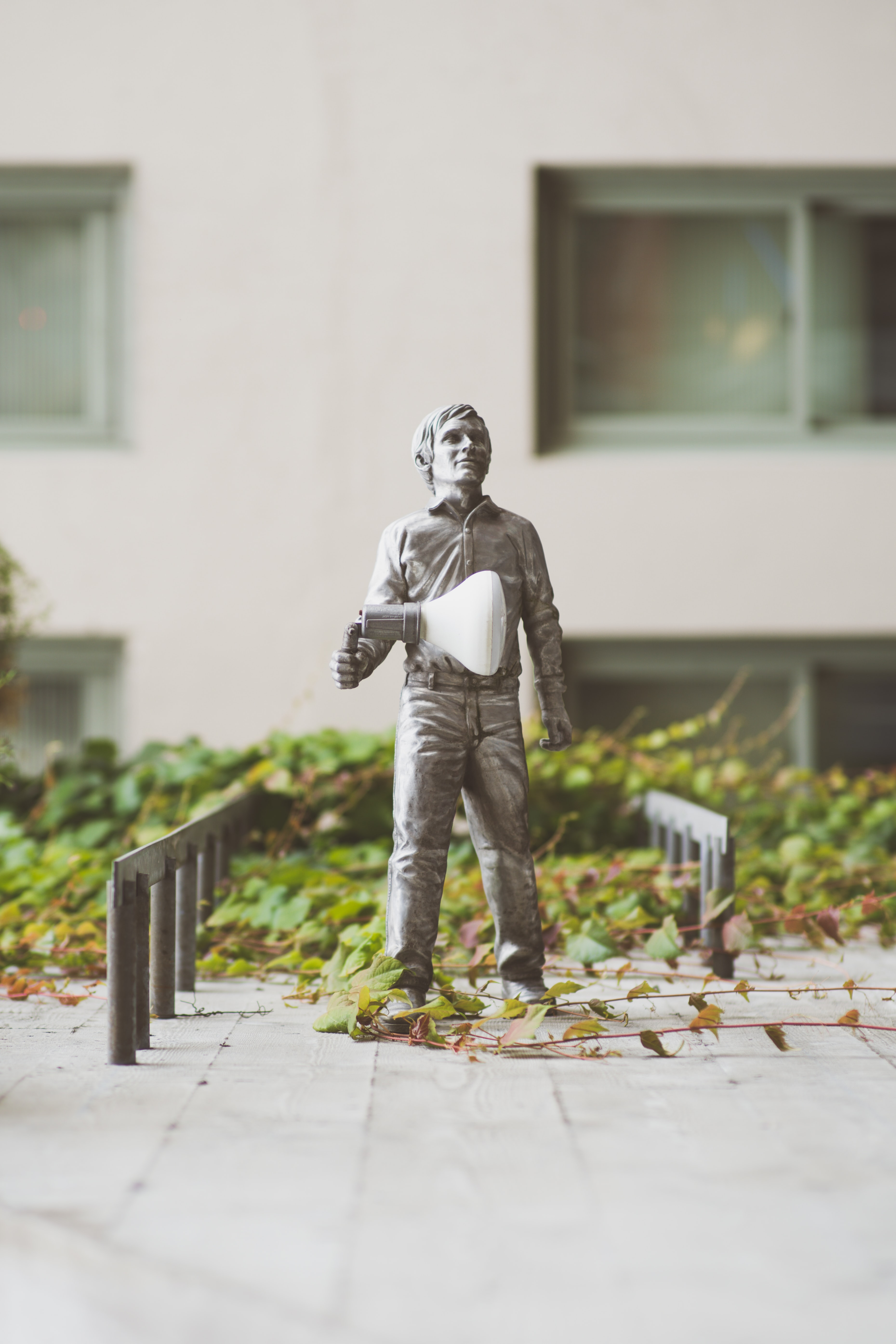 man holding bulb statue near building