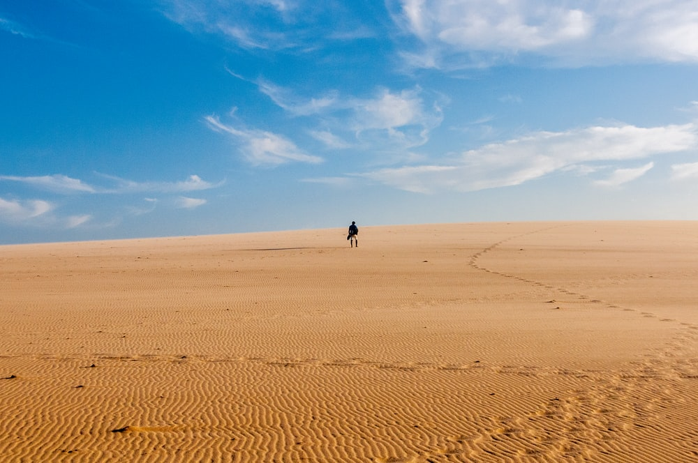 person standing on desert at daytime