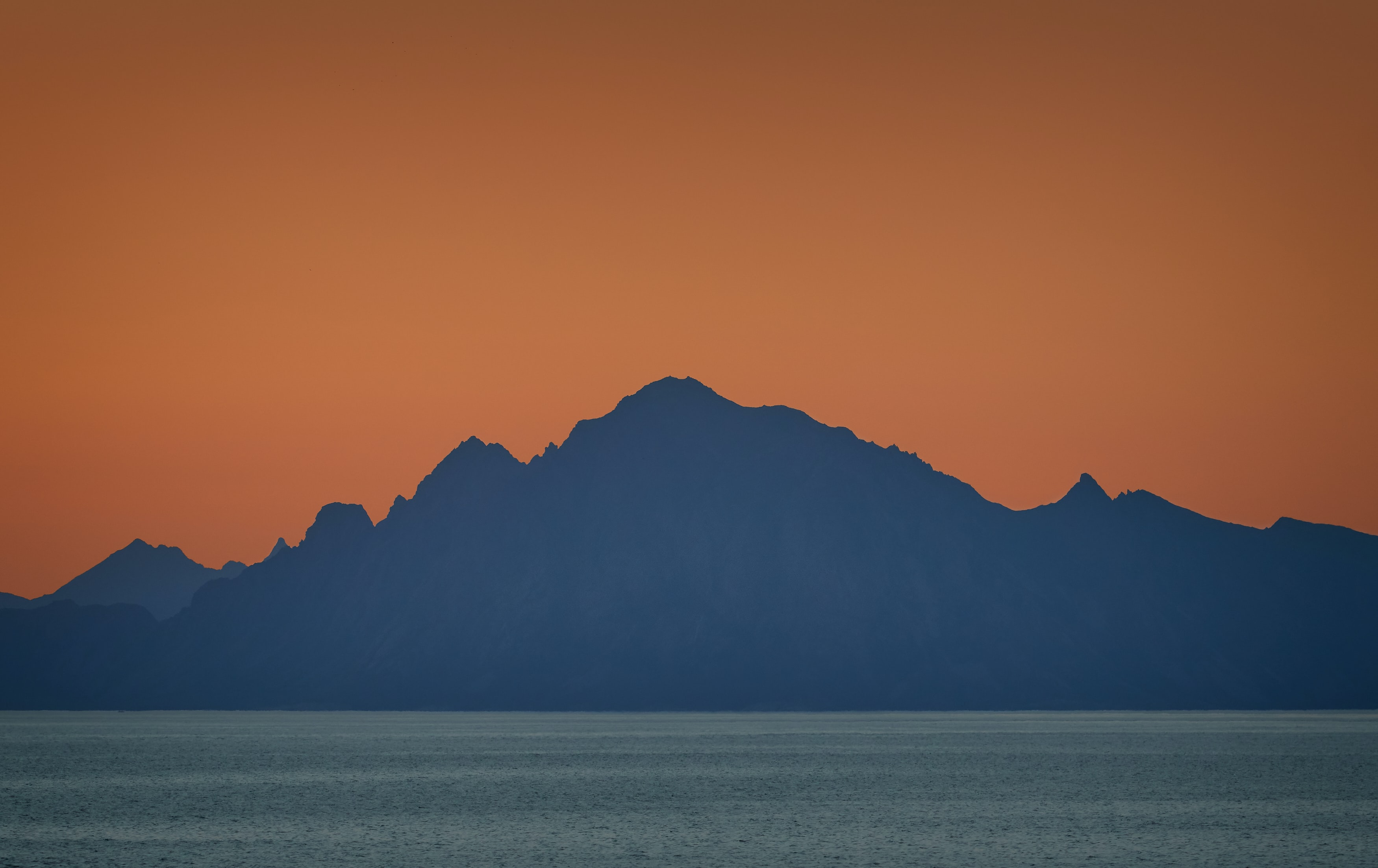silhouette of mountain by the sea