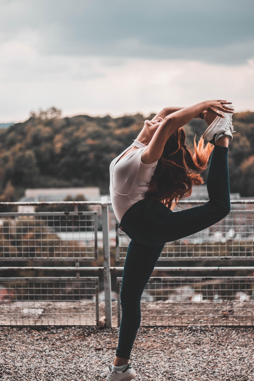woman making stunts near white grilles