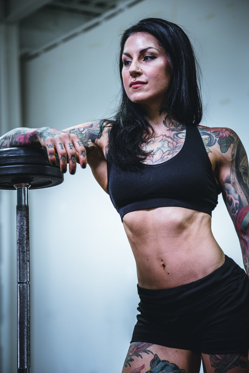 woman leaning on black steel barbell