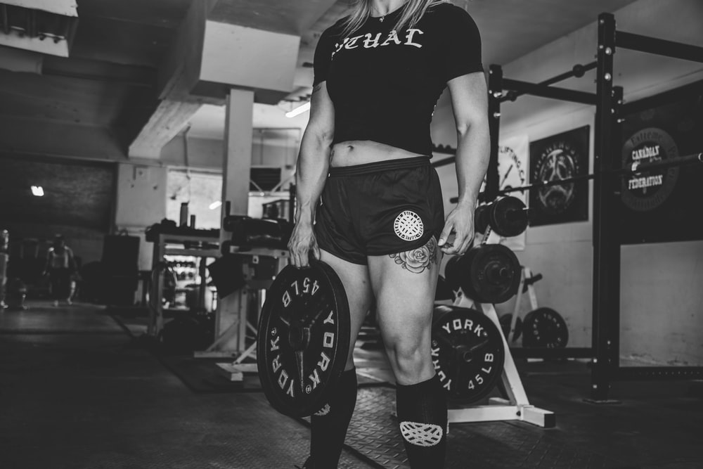 person holding barbell plate