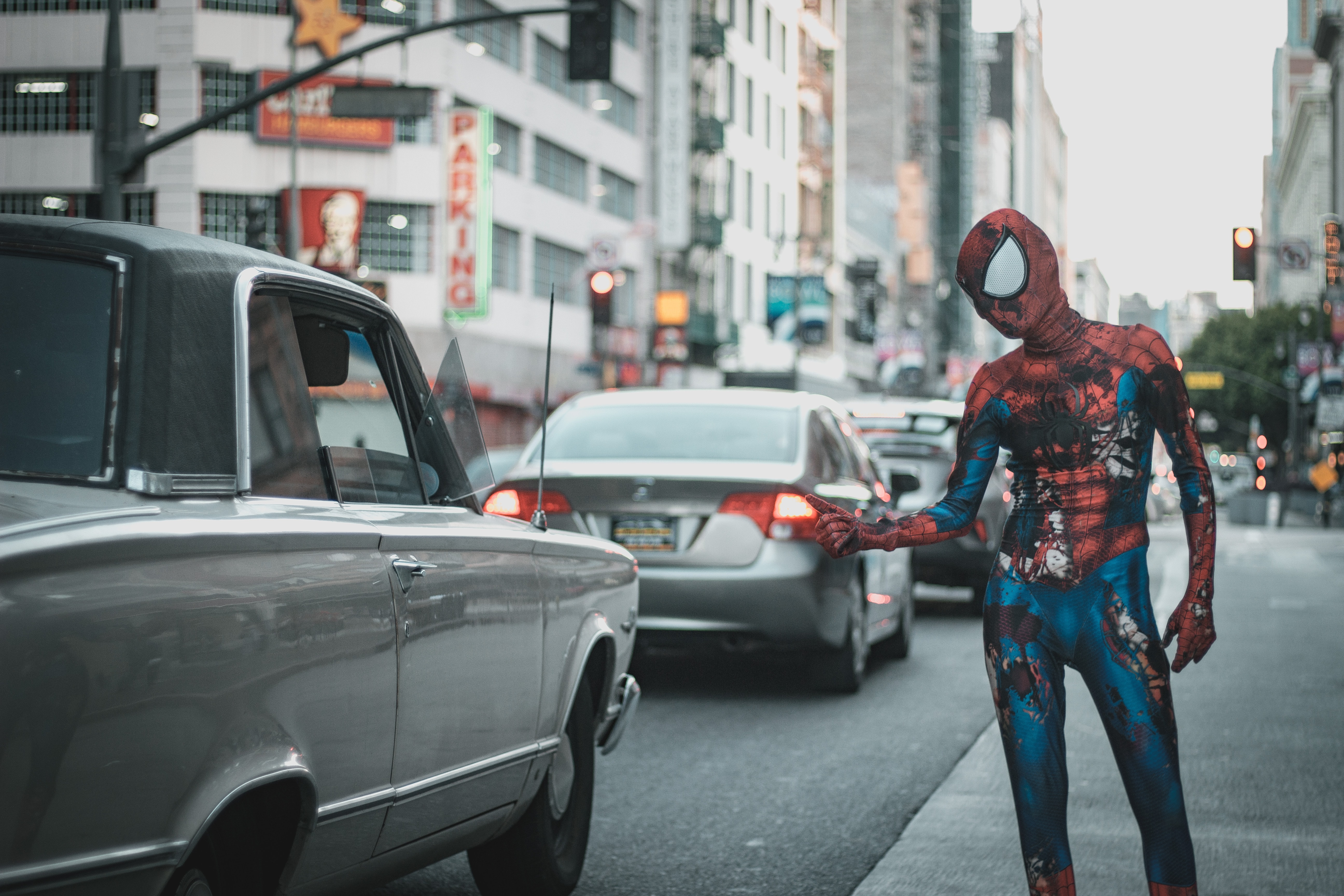 man wearing Spider-Man costume standing on sidewalk with cars on roadway