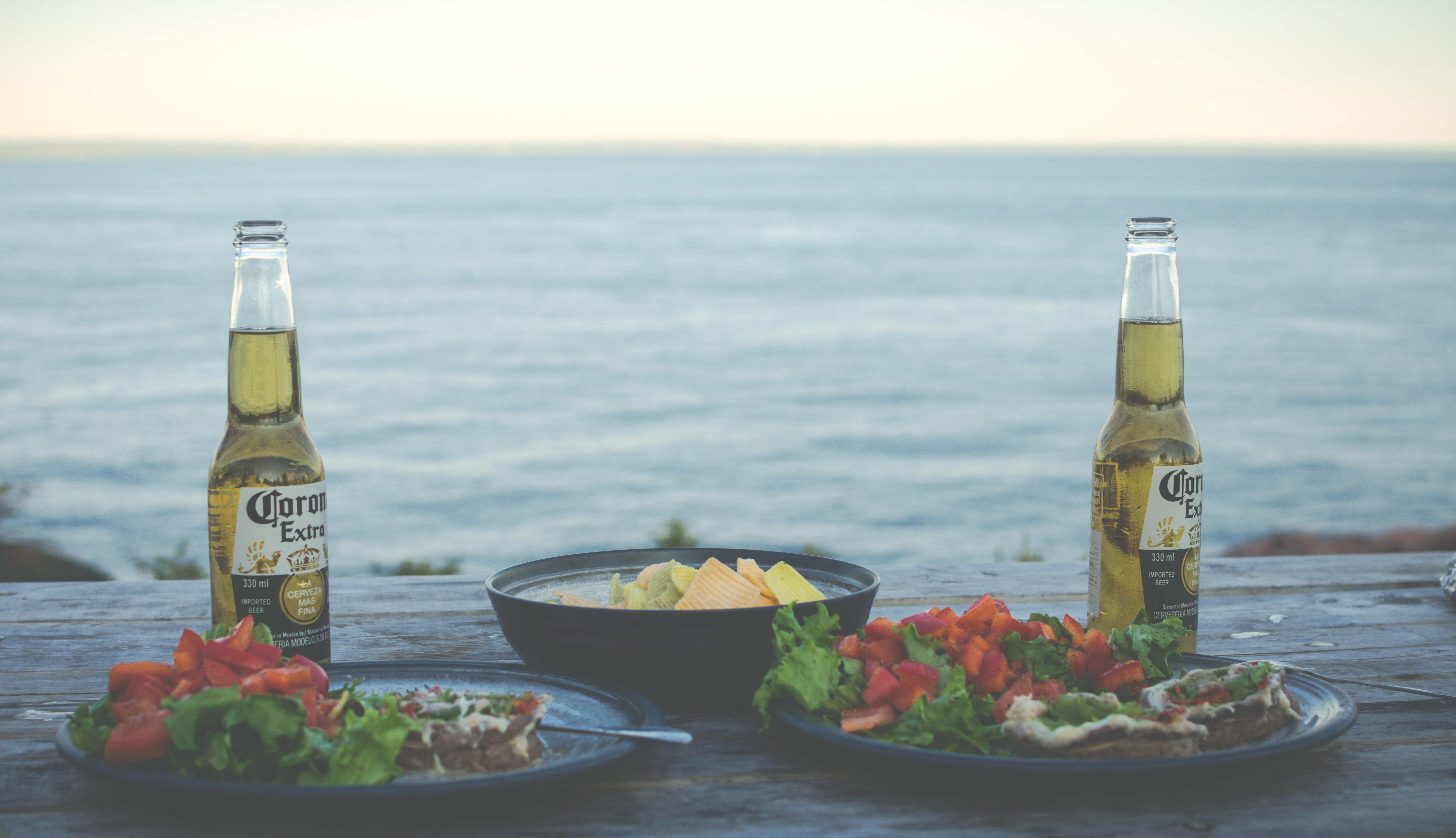 two Corona Extra bottles near cook food