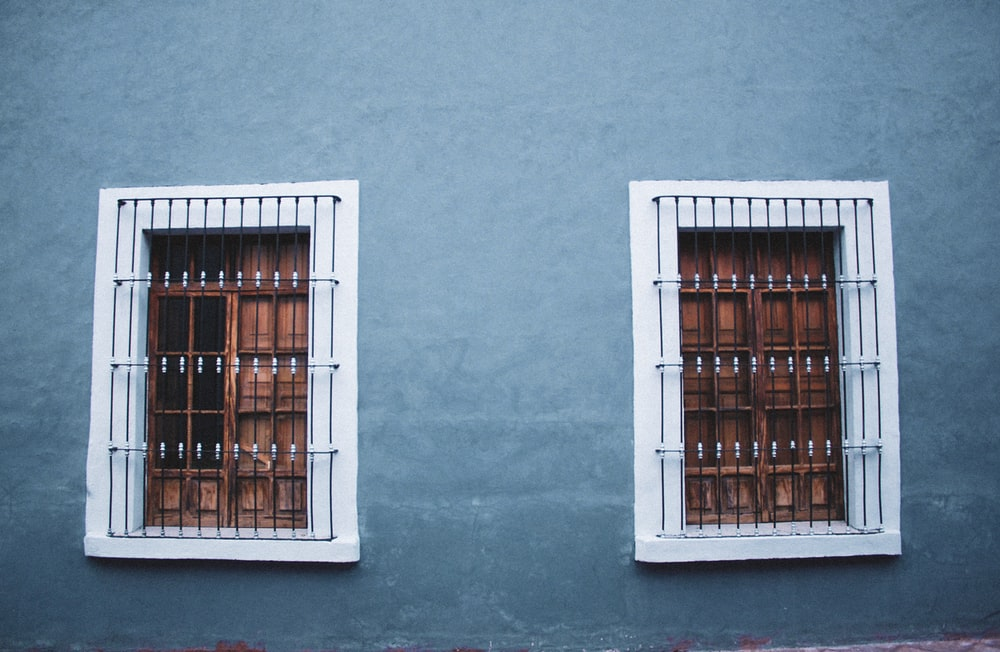 two opened white wooden windows with grilled