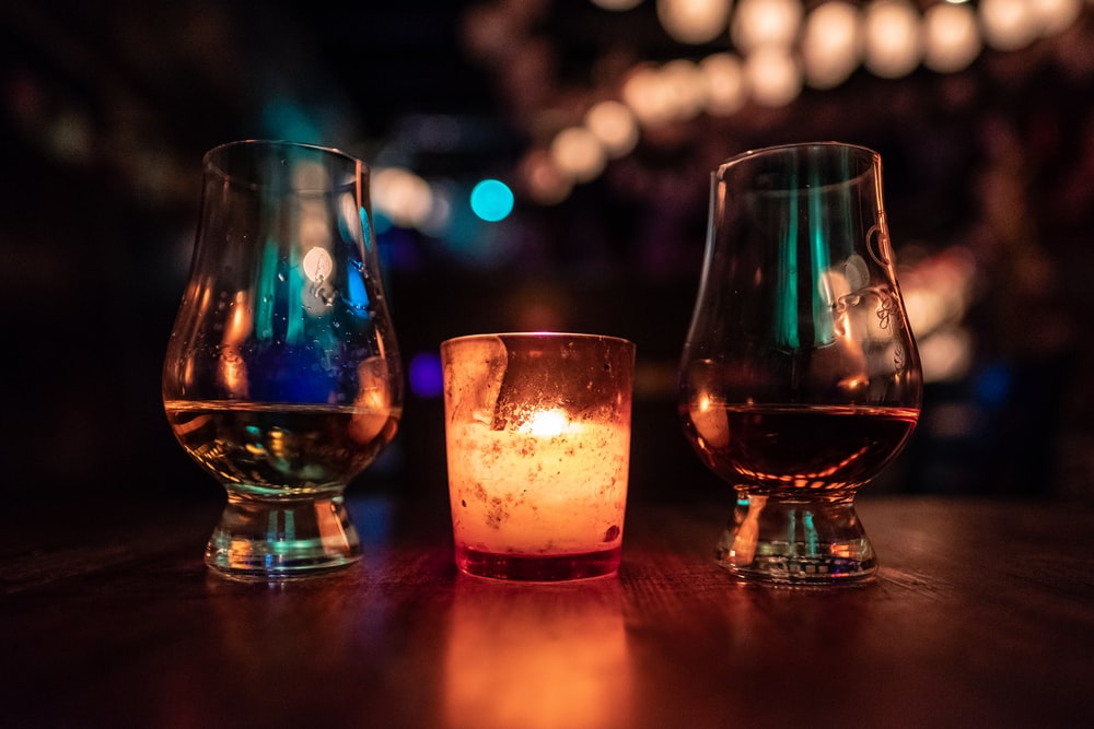 selective focus photography of two clear footed glasses placed near votive candle on table