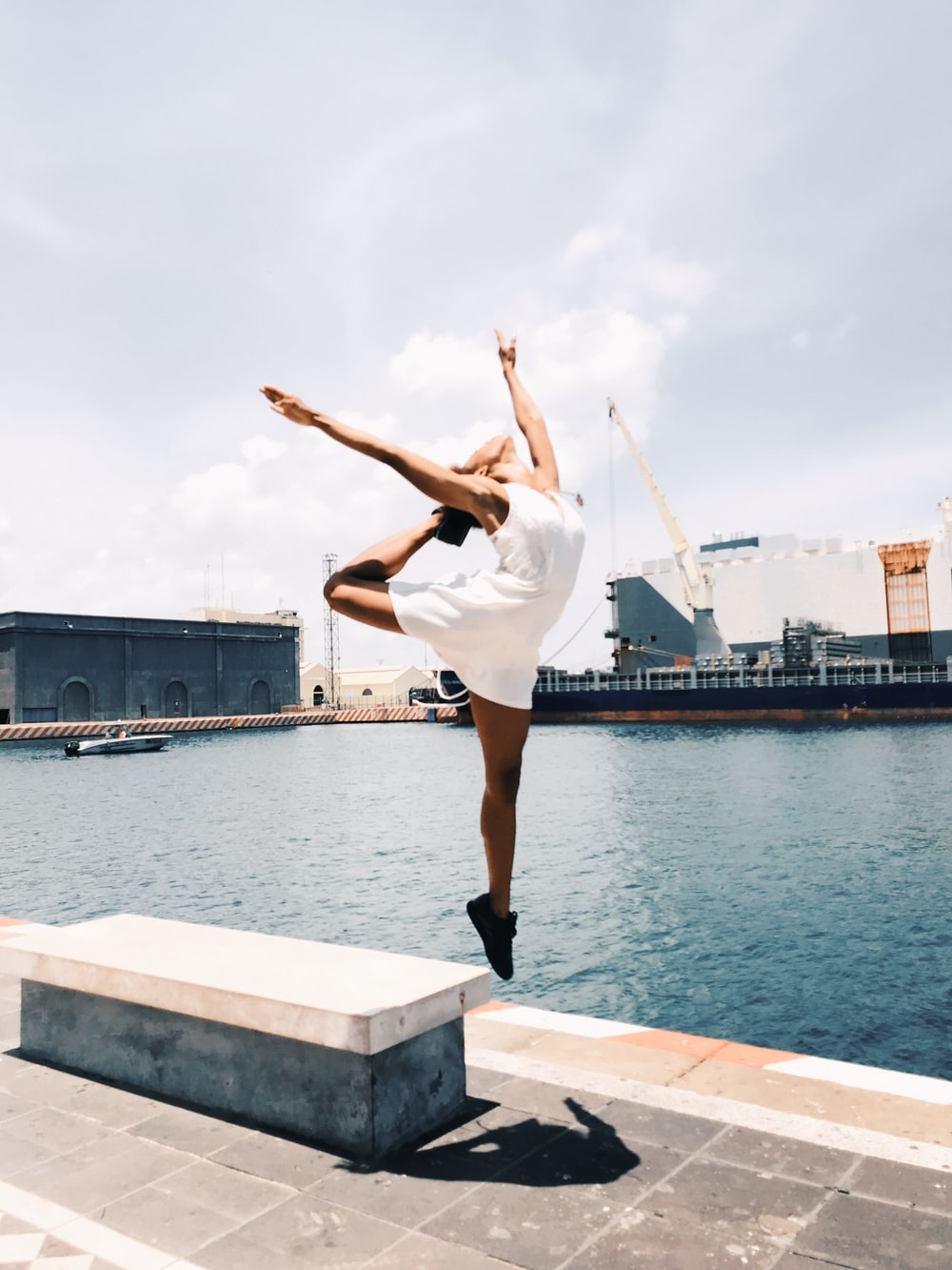 woman jumping in mid-air near body of water during daytime