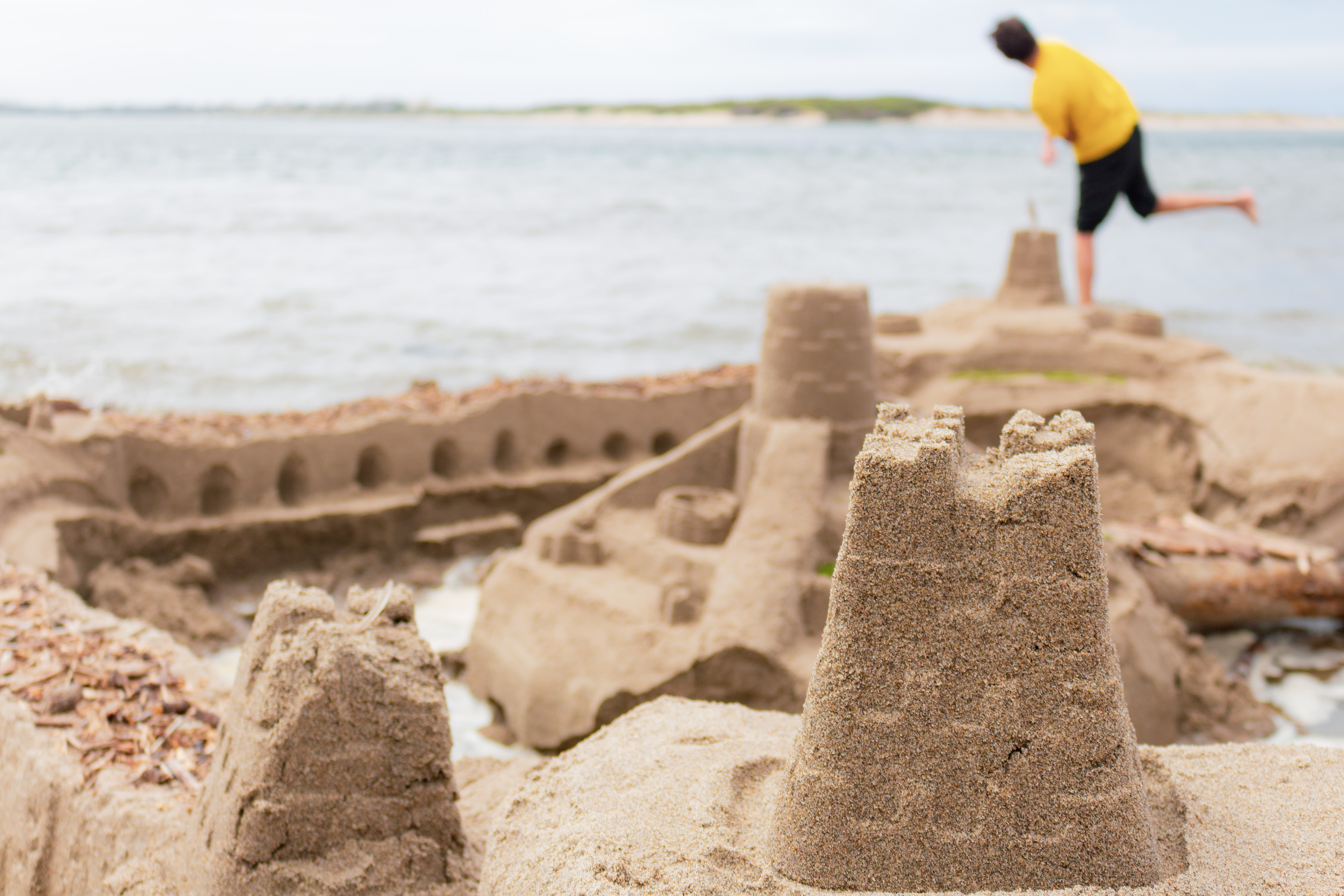 selective focus photography of sand castle near man standing on seashore