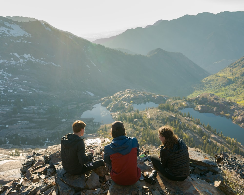 two men and one woman sitting on cliff overlooking lake and mountains during daytime