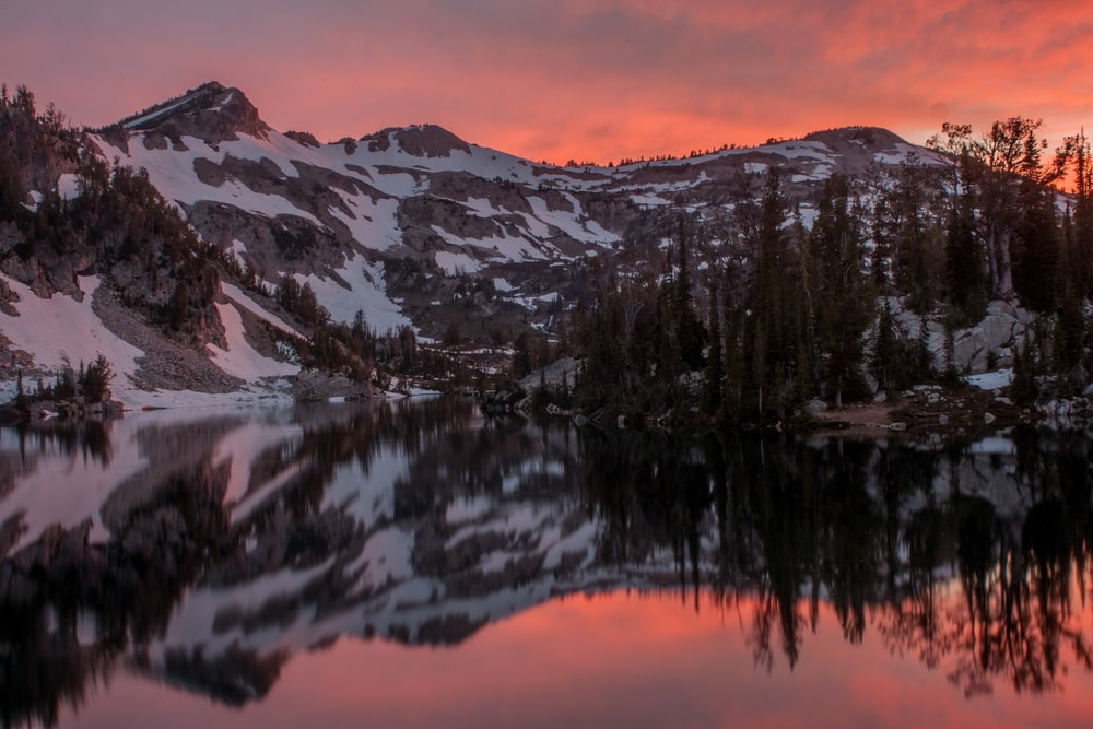 snow covered by mountain near river under sunset