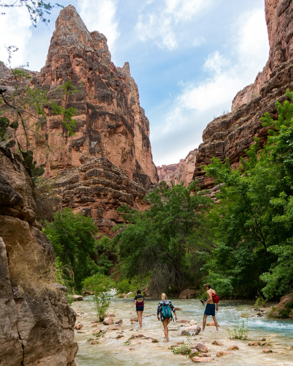 three person walking on the river besides the mountain