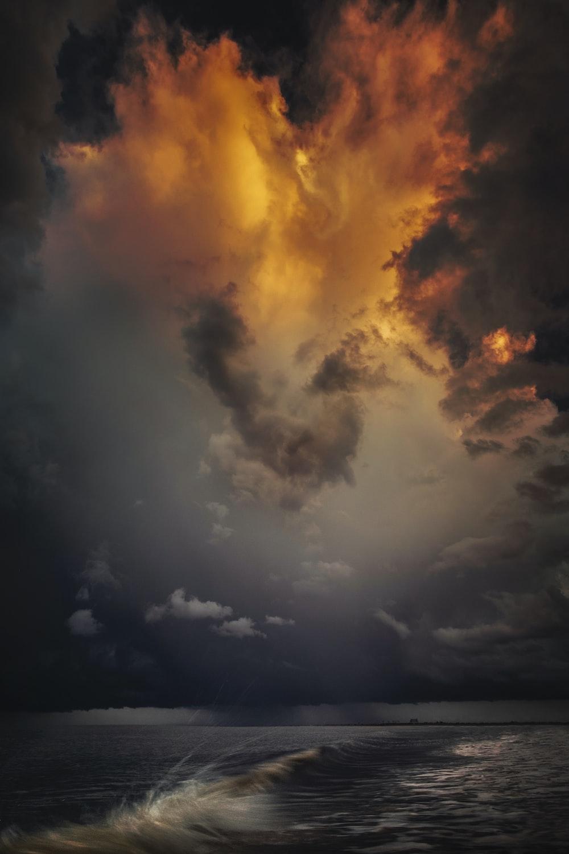 blue sea under orange cloudy sky