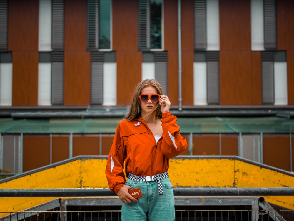 woman standing beside grill while holding sunglasses