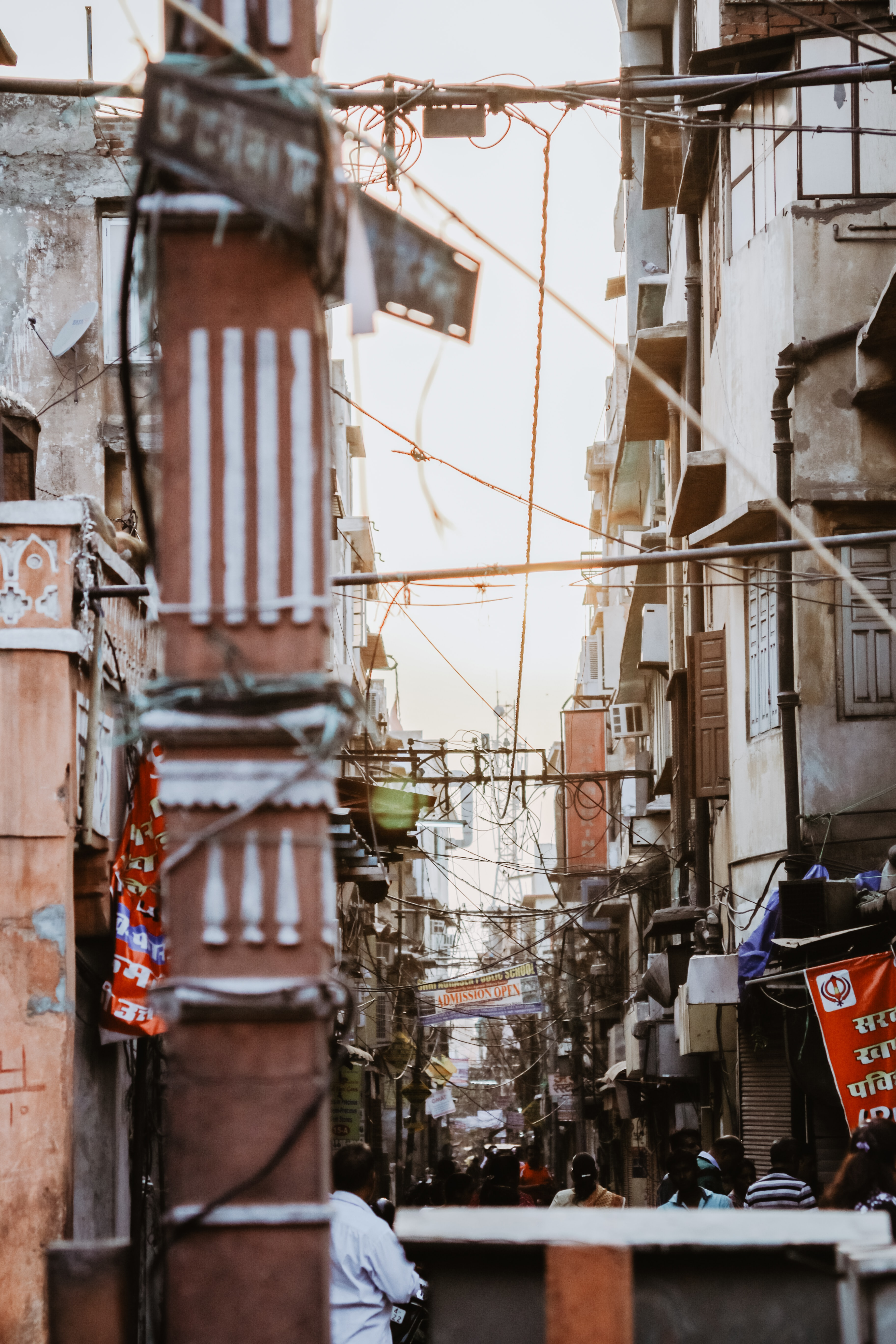 people in alley in middle of buildings under cables
