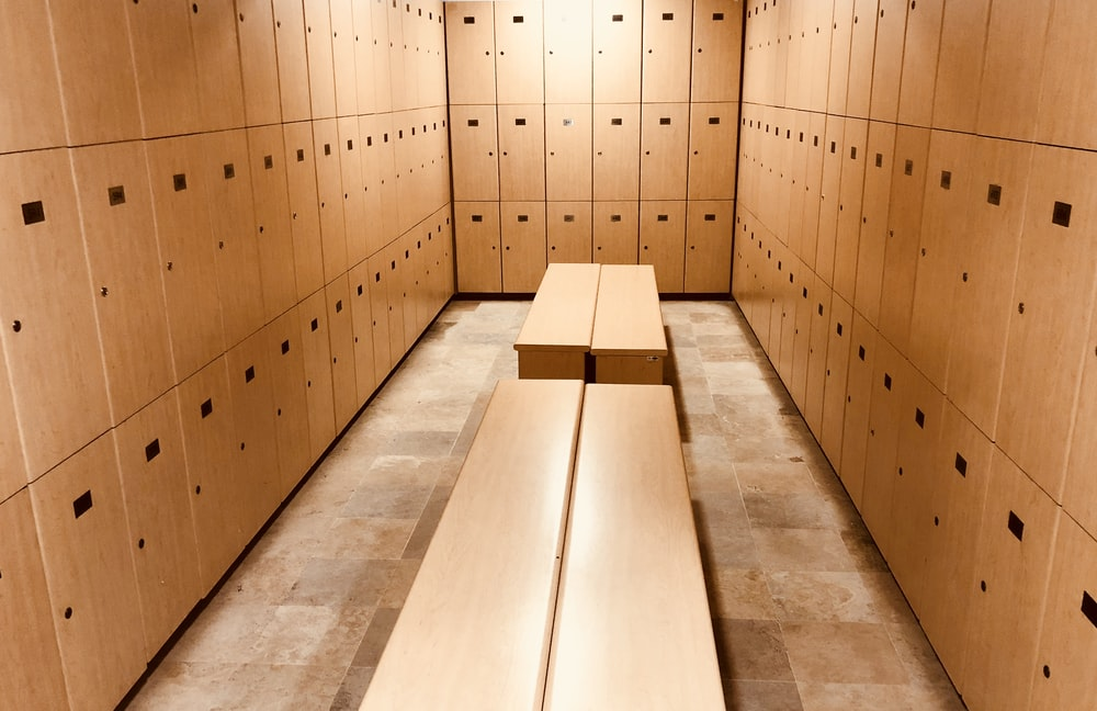 four brown wooden benches inside locker room