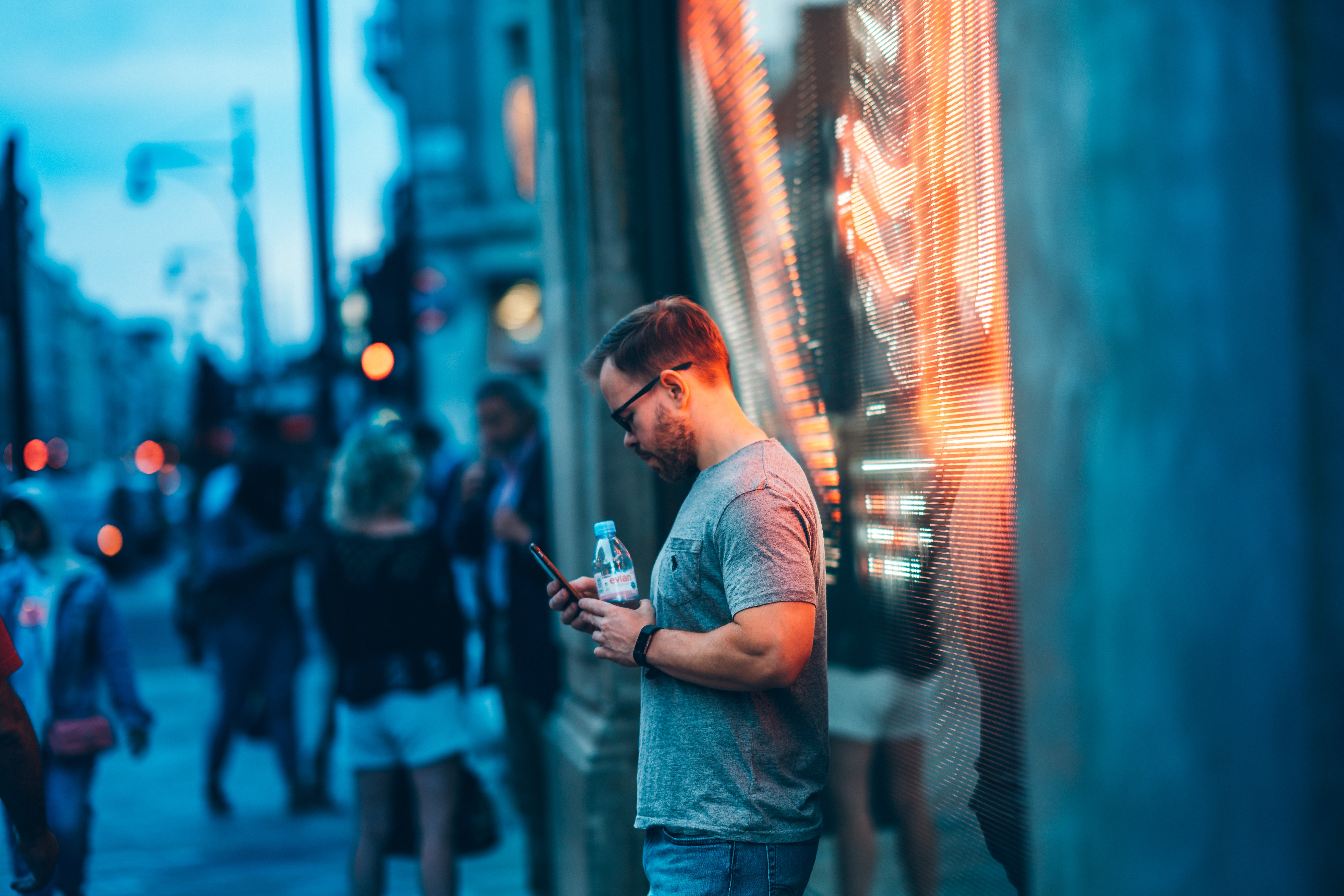 man standing beside wall holding smartphone and water bottle