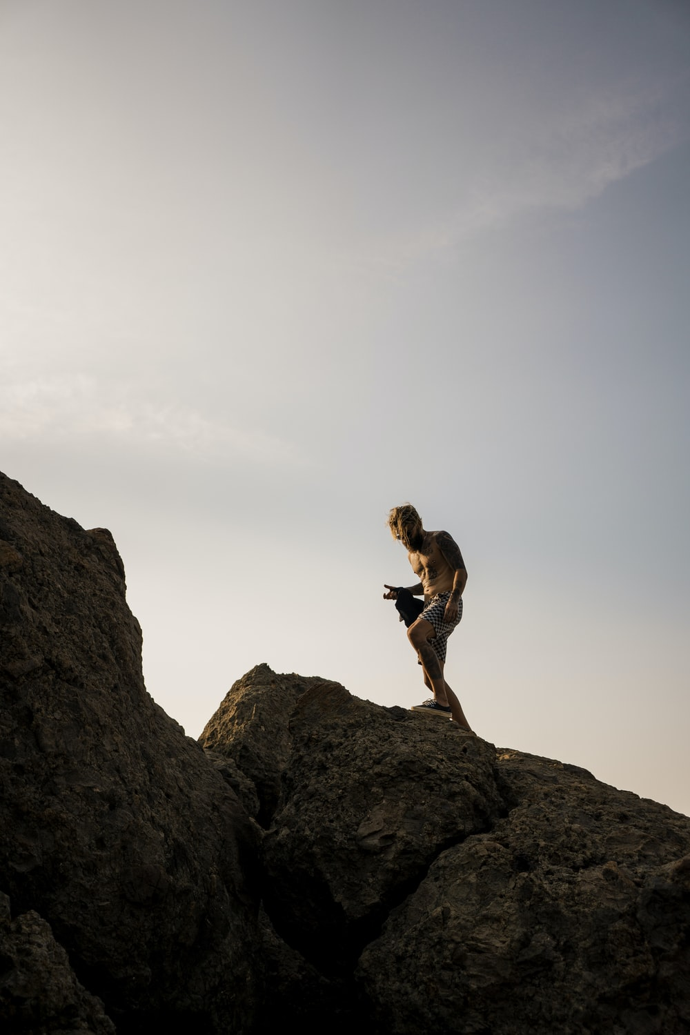 man wearing white shorts standing on brown rocks under clear blue sky