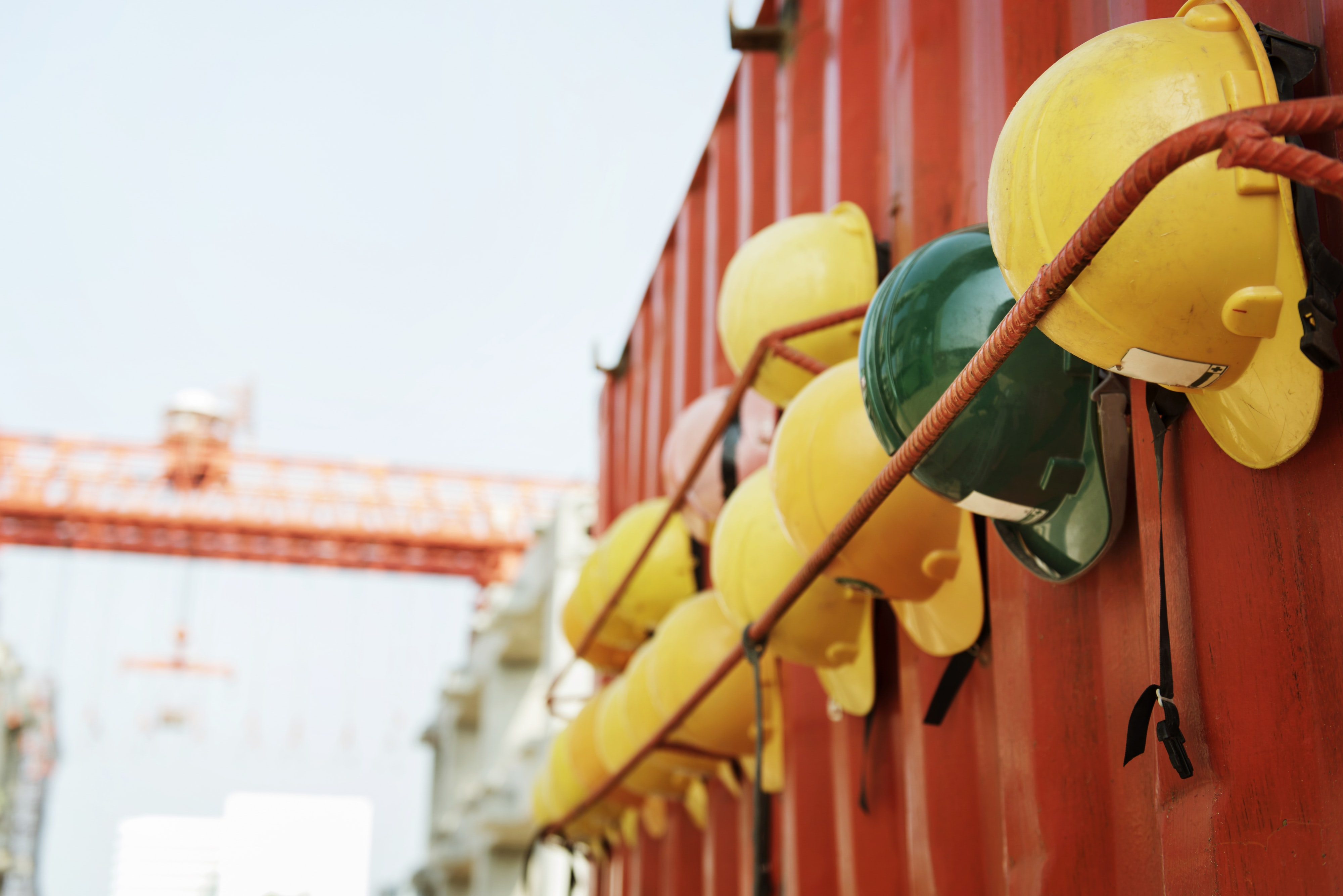 assorted-color hard hat beside intermodal container