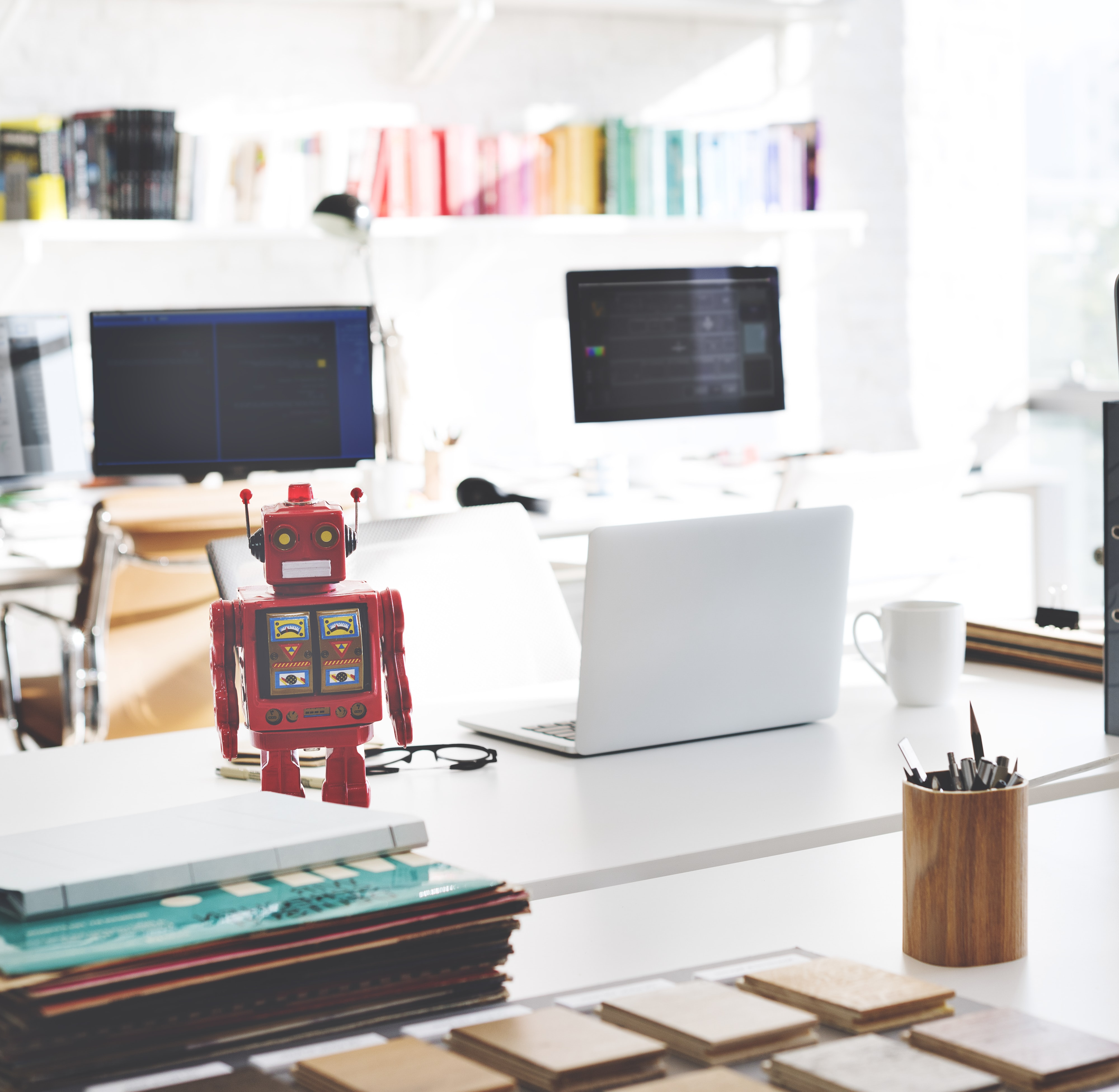 opened white laptop computer beside red robot toy