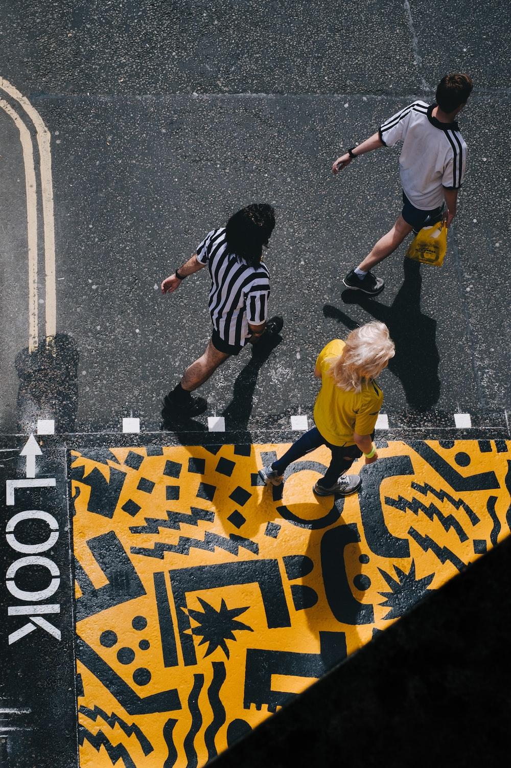 three people walking on road