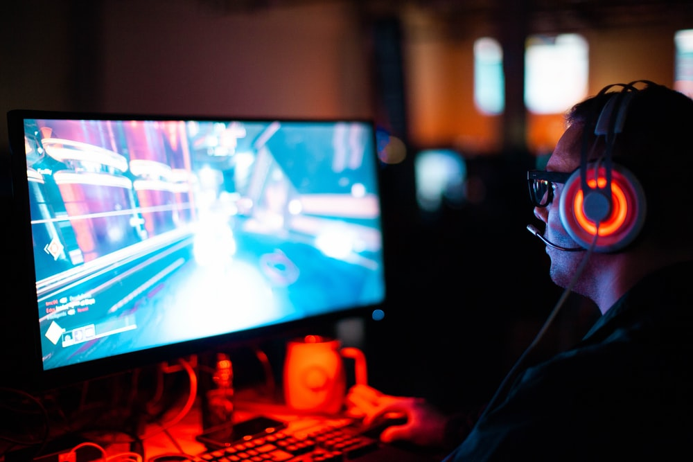 person using computer playing FPS game