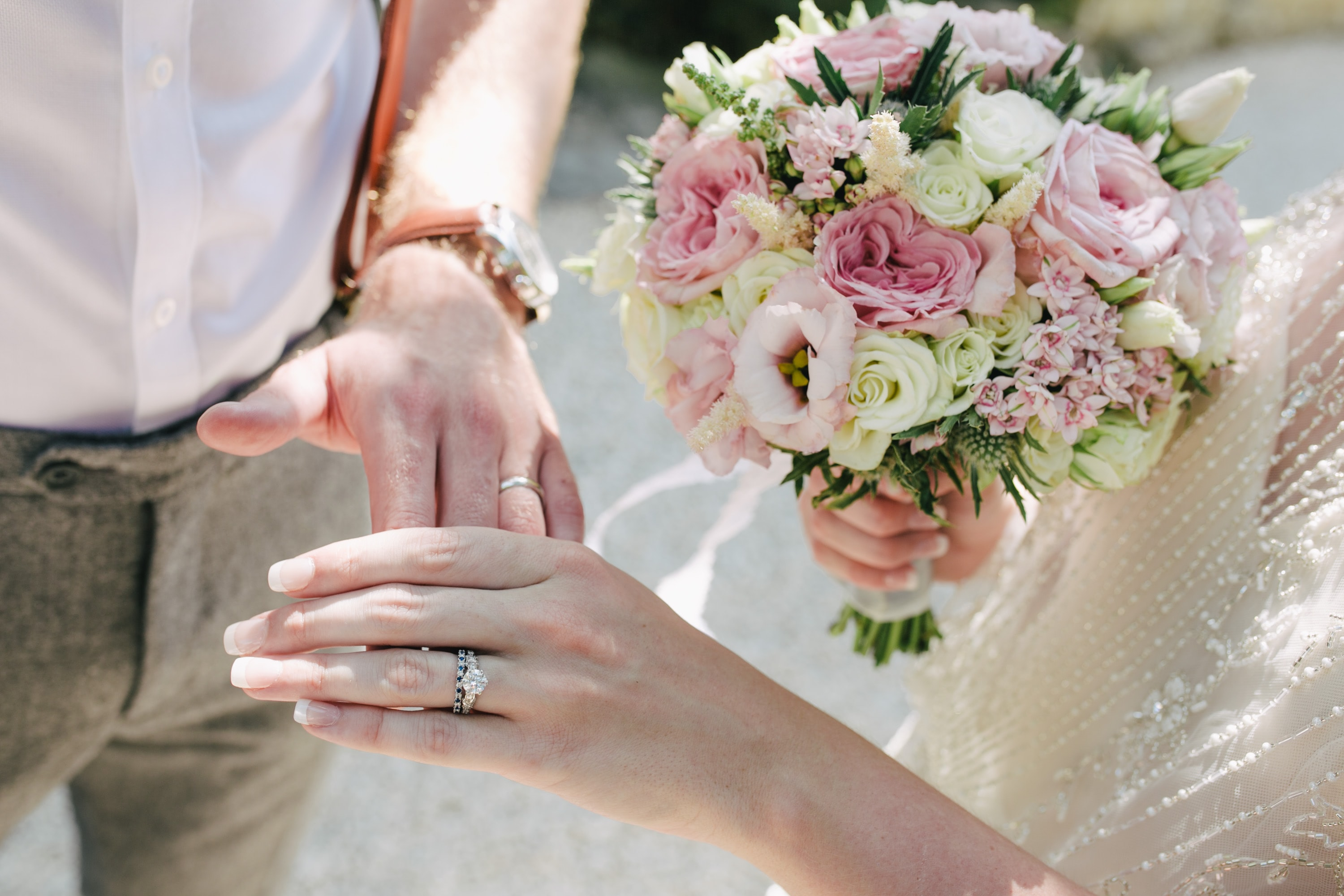 woman holding bouquet of flowers holding man's hand
