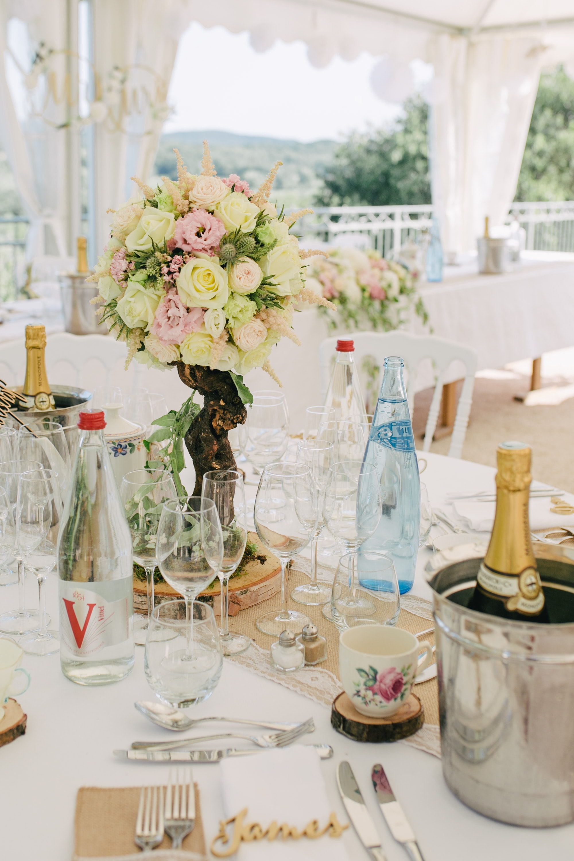 wine glass, bottles, and bouquet of flowers on table