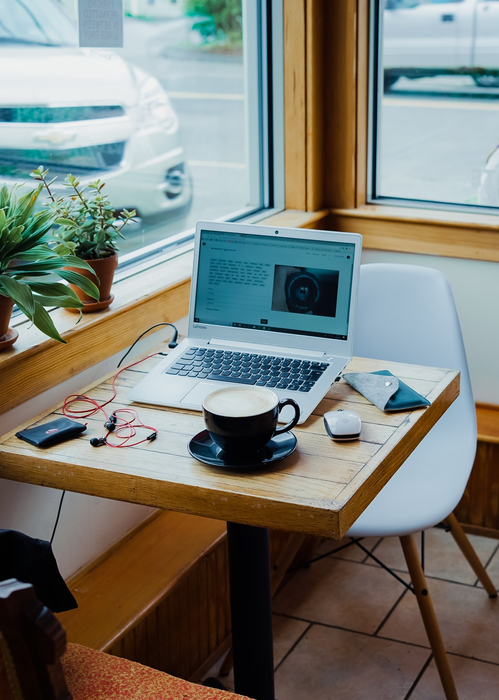 cup of coffee, laptop computer, and red earphones plugged in laptop on brown wooden table