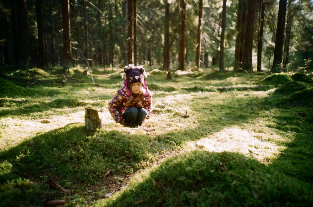 girl sitting in the middle of green woods