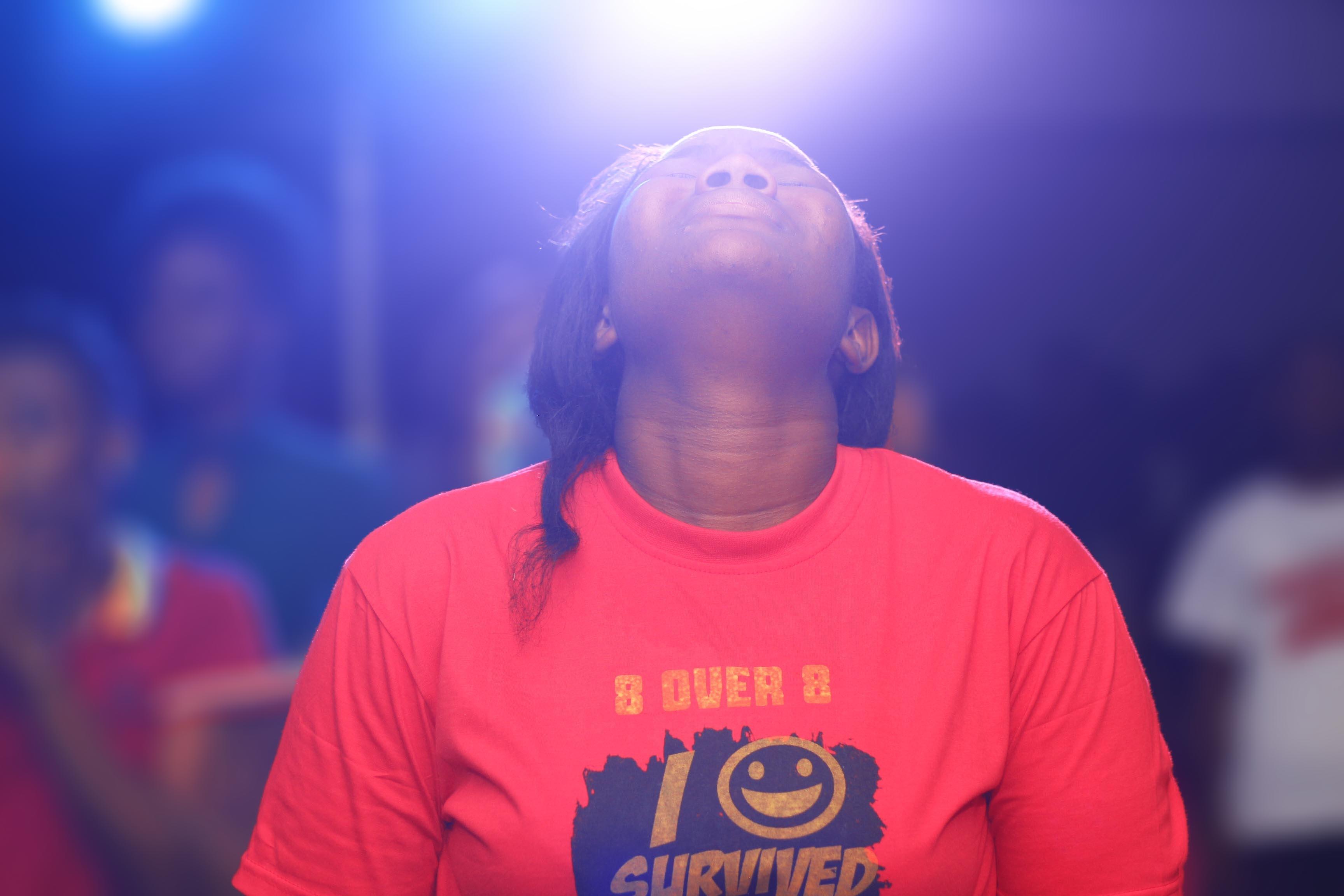 woman wearing crew-neck t-shirt facing upward while closing her eyes