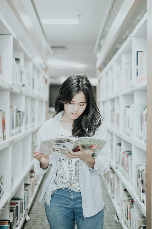 woman reading book on pathway between book shelf